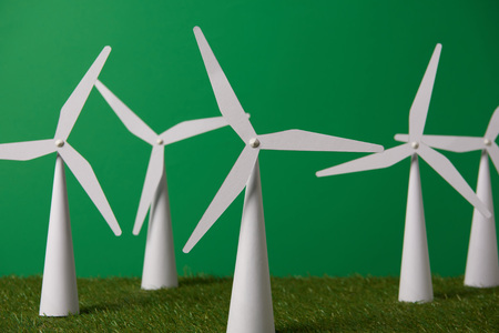 white windmill models on grass and green background