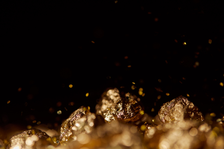 selective focus of golden stones with sparkling lights isolated on black