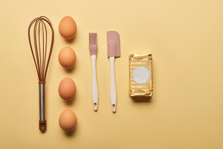 flat lay with balloon whisk, eggs, spatula, bakery brush and butter on yellow background