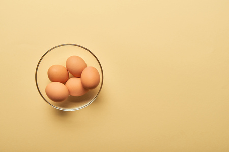 top view of fresh eggs in glass bowl on yellow background Stock Photo