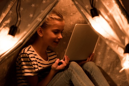 Cheerful kid using laptop in wigwam at home