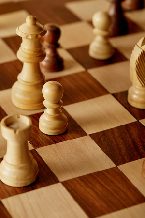 selective focus of wooden chess pieces on chess board