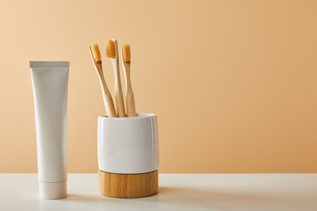 bamboo toothbrushes in holder and toothpaste in tube on white table and beige background