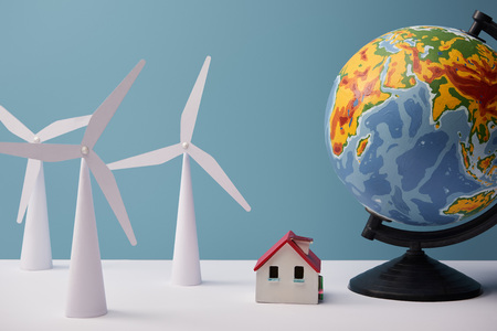 windmill and house models with big globe on white table and blue background 스톡 콘텐츠