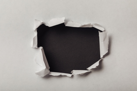 torn hole in sheet of paper on black background