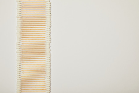 top view of cotton ear sticks laid out vertically on white background