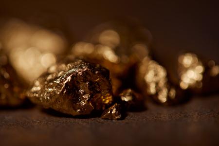 selective focus of golden stones on blurred background Imagens