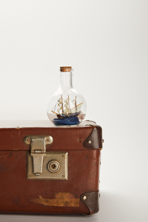 toy ship in glass bottle on brown suitcase with copy space