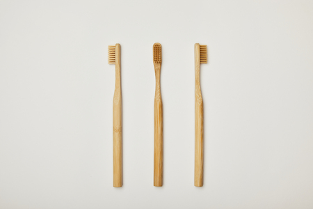 top view of bamboo toothbrushes on white background