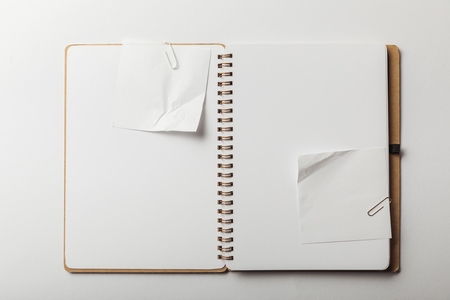top view of notebook with white sticky notes and paper clips on white background