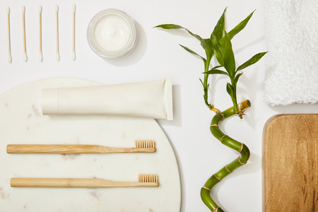 top view of marble round board with bamboo toothbrushes and toothpaste in tube, cosmetic cream, ear sticks, bamboo stem and towel on white background