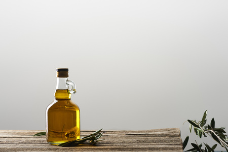 bottle of oil and olive tree leaves isolated on grey
