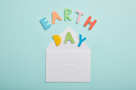 top view of colorful paper letters and and envelope on turquoise background, earth day concept