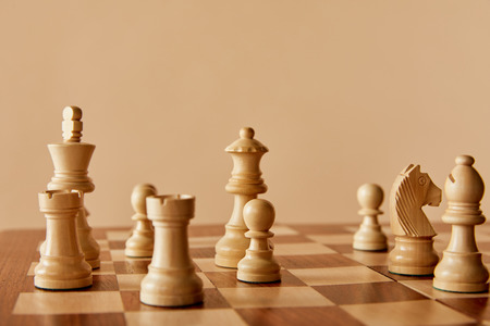 wooden chess on chess board and beige background