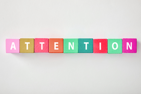 top view of attention lettering made of multicolored cubes on grey background Stock fotó