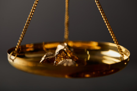 selective focus of golden stones on scales on dark background