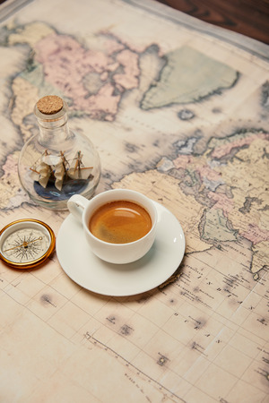 coffee cup and saucer, compass and toy ship in glass bottle on map Banque d'images - 118589451