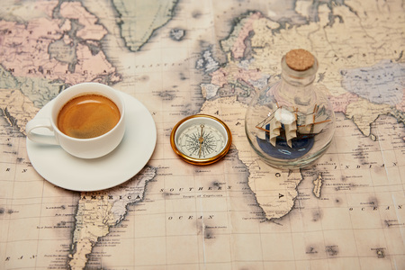 selective focus of coffee cup and saucer, compass and toy ship in glass bottle on map Banque d'images - 118535436