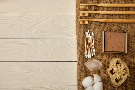 flat lay of different hygiene and care items arranged on sackcloth on white wooden surface, zero waste concept Stok Fotoğraf