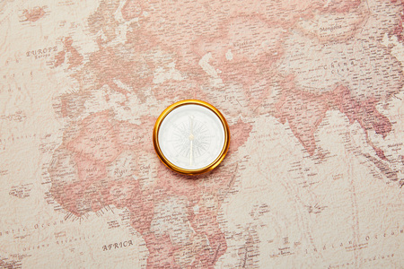 top view of golden compass on vintage world map Stock Photo