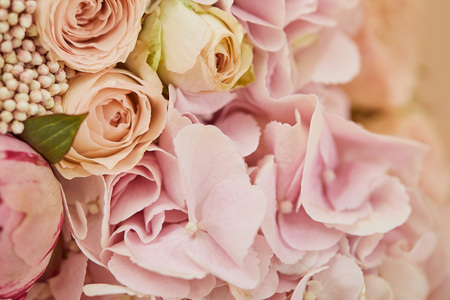 close up of bouquet of roses and pink peonies on table