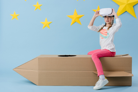 Kid sitting on cardboard rocket and taking off vr headset on blue starry background