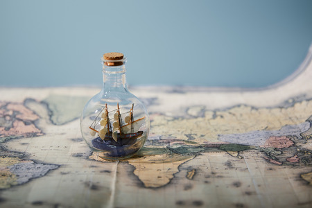 Selective focus of toy ship in glass bottle and map with copy space isolated on blue Foto de archivo
