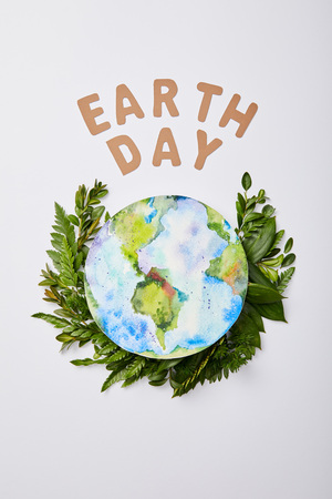 top view of fresh green fern leaves with paper letters and planet picture isolated on grey background, earth day concept Stockfoto