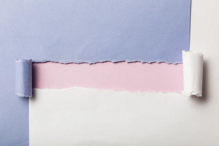 torn blue and white papers with rolled edges on pink background