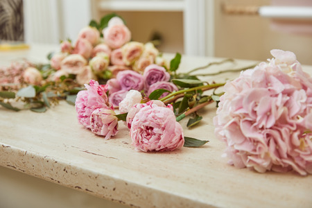 selective focus of pink roses and peonies on surface