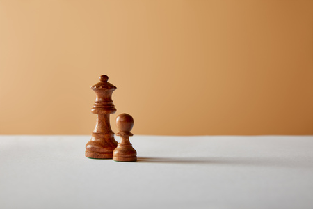 wooden queen and pawn pieces on white table and beige background 写真素材