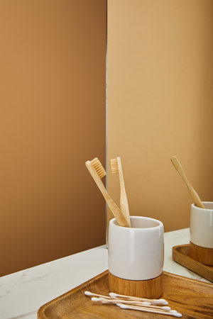 board with bamboo toothbrushes in holder, ear sticks and mirror on white marble table and beige background 写真素材