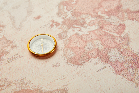 golden compass on vintage world map