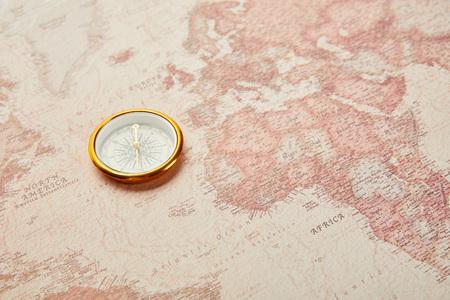 golden compass on vintage world map