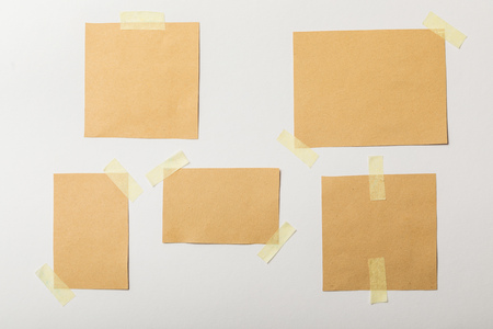 brown blank papers with sticky tape on white background