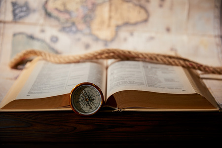 Selective focus of rope, map, book and compass on wooden table