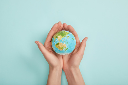 top view of woman holding planet model on turquoise background, earth day concept