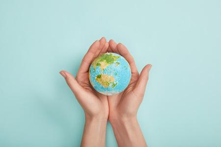 vista dall'alto della donna che tiene il modello del pianeta su sfondo turchese, concetto della giornata della terra