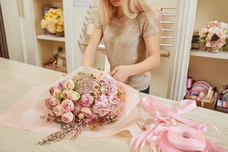 partial view of florist making bouquet of roses and peonies at workspace Stok Fotoğraf