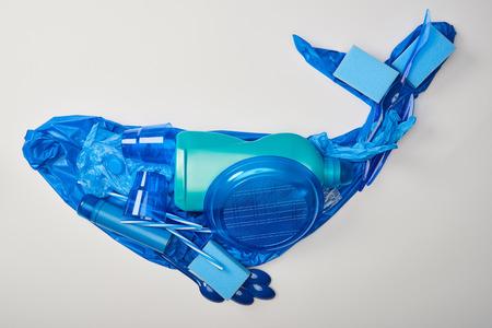 Vista superior de la ballena hecha de vajilla de plástico desechable, bolsa, botella, esponjas y guantes de goma aislados en blanco Foto de archivo