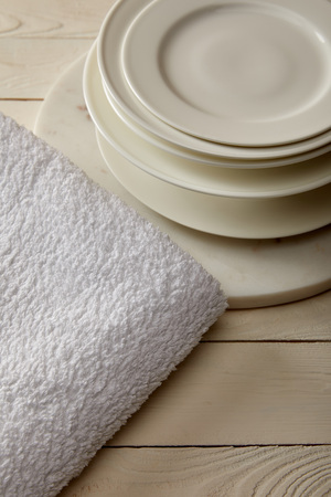 stacked plates and white terry cotton towel on white wooden surface