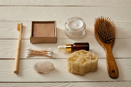flat lay of hygiene and cosmetic items on white wooden surface, zero waste concept