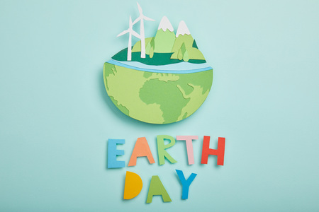 top view of paper cut planet with renewable energy sources and colorful paper letters on turquoise background, earth day concept Reklamní fotografie