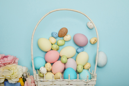 Top view of easter chicken and quail eggs in straw basket and flowers Foto de archivo - 118536041