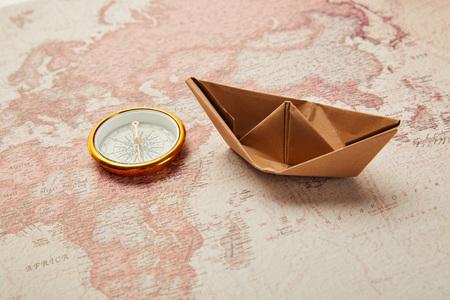 boussole dorée et bateau en papier sur la carte du monde rétro