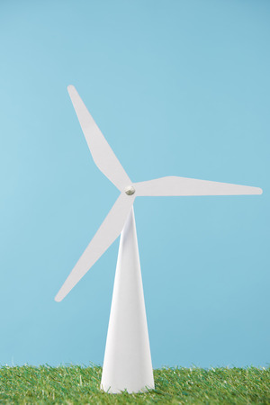 white windmill model on green grass and blue background