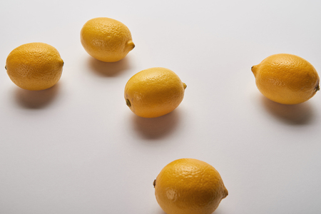 yellow ripe whole scattered lemons on grey background