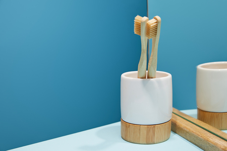 holder with bamboo toothbrushes and mirror on white table and blue background Banco de Imagens