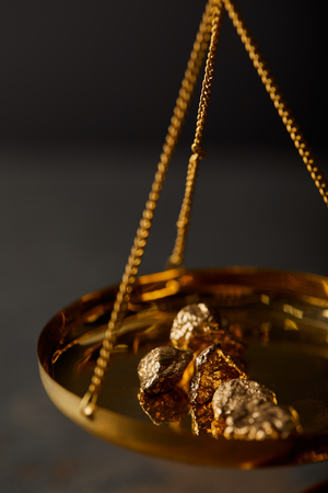selective focus of golden stones on vintage scales on dark background