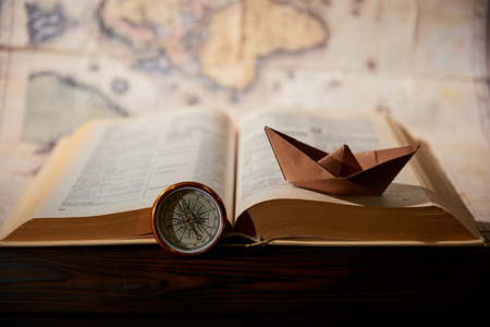 Selective focus of paper boat, book, map and compass on table